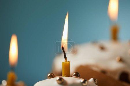 Photo pour Gros plan de gâteau de Pâques décoré avec des aspersions et des bougies allumées sur turquoise - image libre de droit