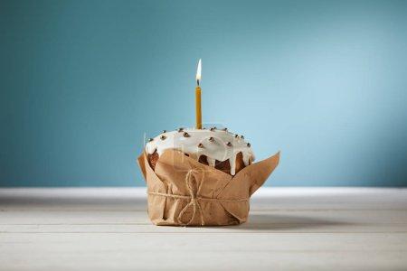 Photo pour Gâteau de Pâques décoré avec des aspersions et une bougie allumée sur turquoise - image libre de droit