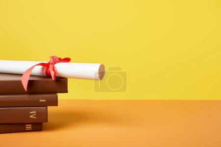 Photo pour Livres et diplôme bruns avec le ruban rouge sur la surface orange d'isolement sur le jaune - image libre de droit
