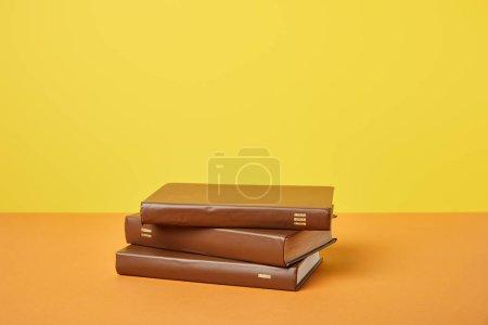 Photo pour Livres bruns sur la surface orange vif d'isolement sur le jaune - image libre de droit