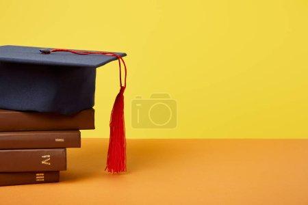 Photo pour Casquette académique et livres bruns sur la surface orange d'isolement sur le jaune - image libre de droit