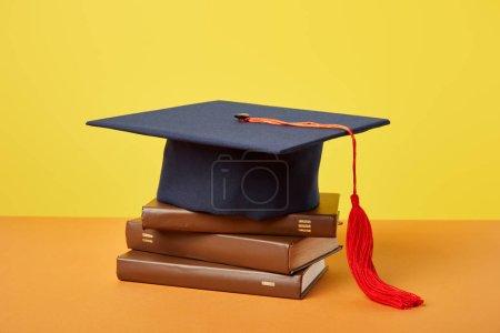 Photo pour Casquette académique et livres bruns sur surface orange isolés sur jaune - image libre de droit