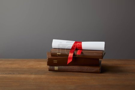 Photo for Brown books and diploma with red ribbon on wooden surface on grey - Royalty Free Image