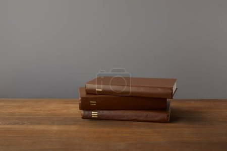 Photo for Three brown books on textured wooden surface on grey - Royalty Free Image