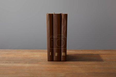 Foto de Libros marrones sobre superficie de madera texturizada aislados en gris - Imagen libre de derechos