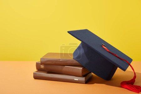 Photo pour Livres bruns et casquette académique avec pompon rouge sur la surface orange d'isolement sur le jaune - image libre de droit