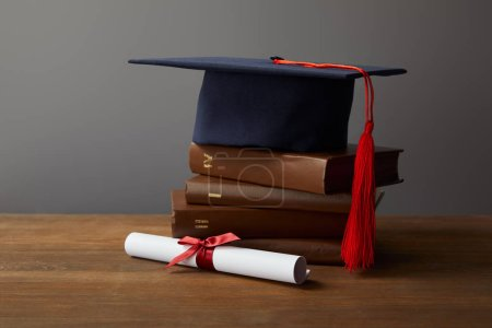 Diploma, academic cap and books on wooden surface on grey