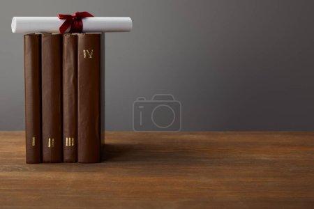 Photo pour Livres et diplôme bruns avec le ruban rouge sur la surface en bois sur le gris - image libre de droit