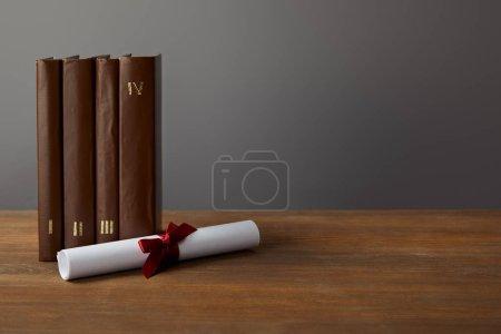Photo pour Livres et diplômes marron avec ruban rouge sur la surface en bois sur gris - image libre de droit