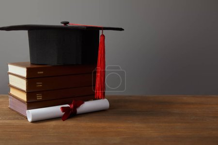 Photo for Diploma, academic cap and books on wooden surface on grey - Royalty Free Image