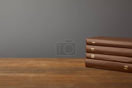 Photo pour Quatre livres bruns sur la surface en bois texturé sur le gris - image libre de droit