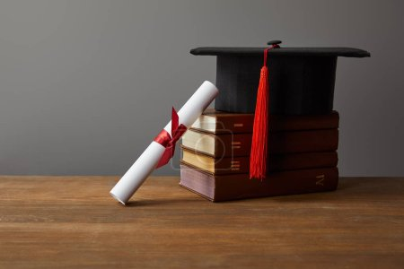 Photo for Diploma, academic cap and books on wooden surface isolated on grey - Royalty Free Image