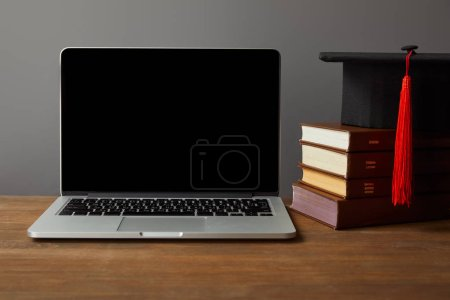 Photo for Laptop with blank screen, books and academic cap on wooden surface isolated on grey - Royalty Free Image