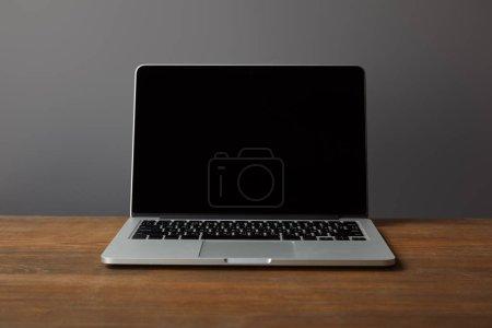 Photo pour Ordinateur portatif avec l'écran blanc sur la surface en bois brune d'isolement sur le gris - image libre de droit