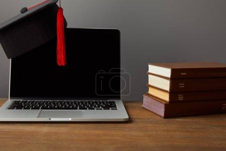 Photo pour Ordinateur portatif avec l'écran blanc, livres et casquette académique avec le gland rouge sur la surface en bois d'isolement sur le gris - image libre de droit
