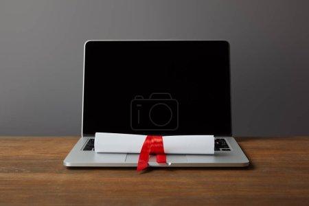Photo pour Ordinateur portatif avec l'écran blanc et le diplôme avec le ruban rouge sur la surface en bois sur le gris - image libre de droit
