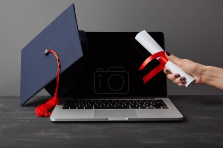 Photo for Cropped view of woman holding diploma near laptop with blank screen and academic cap on grey - Royalty Free Image