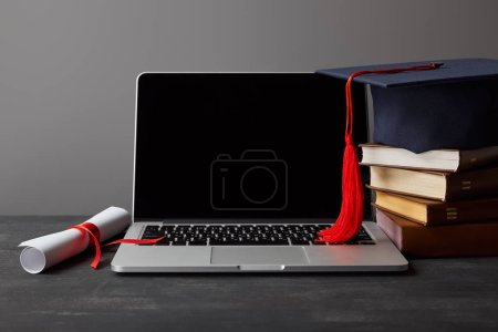 Photo for Laptop with blank screen, diploma, books and academic cap with red tassel isolated on grey - Royalty Free Image