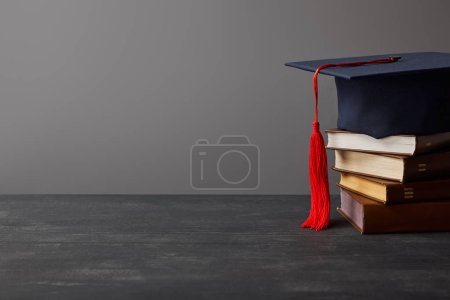 Photo for Brown books and academic cap with red tassel isolated on grey - Royalty Free Image