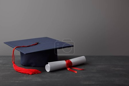 Photo for Diploma and academic cap with red tassel on dark surface on grey - Royalty Free Image