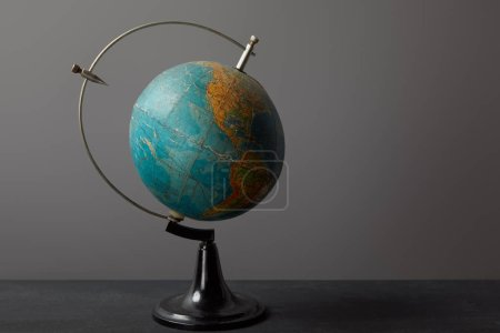 Photo for Old globe on dark shabby textured surface on grey - Royalty Free Image