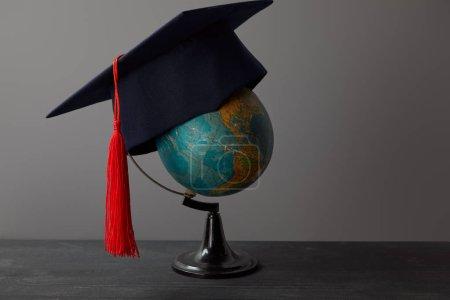Foto de Gorro académico con borla roja en el globo sobre superficie oscura - Imagen libre de derechos