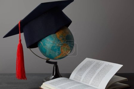 Globe, academic cap with red tassel and open book on texture surface on grey