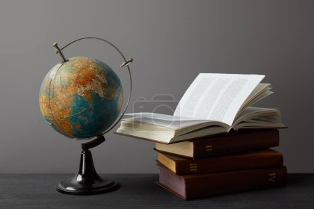 Old globe and books on dark surface on grey