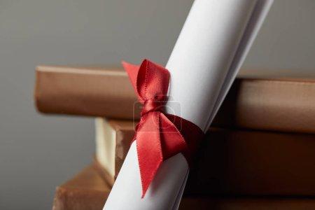 Photo pour Livres et diplôme bruns avec le ruban rouge sur le gris - image libre de droit