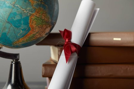 Brown books, globe and diploma with red ribbon on grey