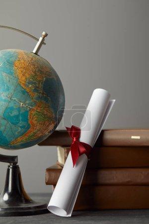 Photo pour Livres bruns, Globe et diplôme avec le ruban rouge sur le gris - image libre de droit
