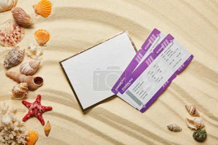 Photo for Top view of blank placard near air tickets and seashells on sandy beach - Royalty Free Image