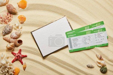 Photo pour Vue du dessus de la plaque vierge près des billets d'avion et des coquillages sur le sable - image libre de droit