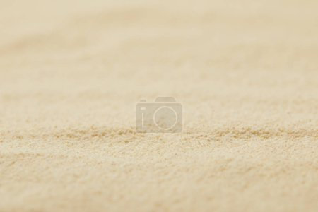 selective focus of textured sandy surface on beach in summertime