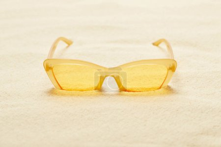 selective focus of yellow sunglasses in sandy beach in summer