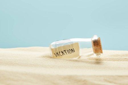 Foto de Botella de vidrio con letras de vacaciones en papel en verano aislado en azul - Imagen libre de derechos