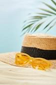 """Постер, картина, фотообои """"селективный фокус желтые солнцезащитные очки возле соломенной шляпе на золотом песке в летнее время изолированы на голубом"""""""