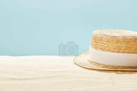 Photo pour Foyer sélectif de chapeau de paille sur la plage de sable en été isolé sur bleu - image libre de droit