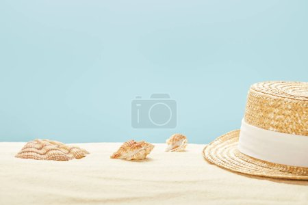 Photo for Selective focus of straw hat near seashells on sandy beach in summertime isolated on blue - Royalty Free Image
