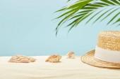 """Постер, картина, фотообои """"селективного фокус соломенной шляпе вблизи ракушек и листьев зеленого пальмы в летнее время изолированы на голубом"""""""