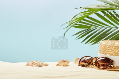 selective focus of sunglasses and straw hat near seashells and green leaves isolated on blue