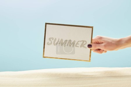 Photo for Cropped view of woman holding card with summer lettering in hand isolated on blue - Royalty Free Image