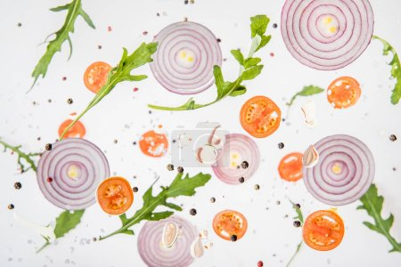 Photo for Background with sliced tomatoes, red onions, garlic, green arugula leaves and spices - Royalty Free Image