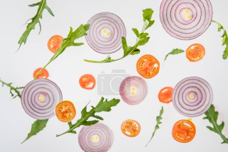 Photo for Background with sliced tomatoes, red onions and green arugula leaves - Royalty Free Image