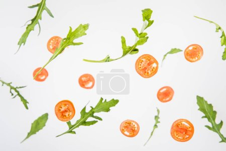 Photo for Sliced red tomatoes and  green arugula leaves on grey background - Royalty Free Image