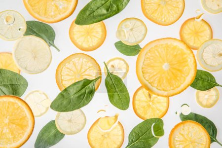 Photo for Bright orange and lemon slices with green spinach leaves on grey background - Royalty Free Image