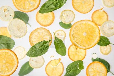 Photo pour Orange douce et tranches de citron avec des feuilles d'épinard vert sur fond gris - image libre de droit