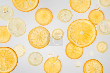 Photo for Bright orange and lemon slices on grey background with water bubbles - Royalty Free Image