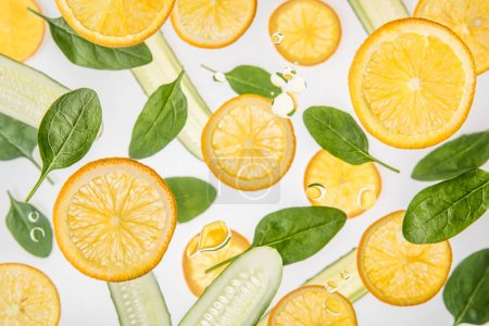 Photo for Fresh orange slices with green spinach leaves and cucumbers on grey background - Royalty Free Image