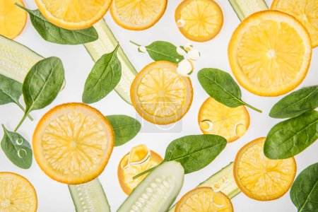 Photo for Orange slices with green spinach leaves and cucumbers on grey background - Royalty Free Image